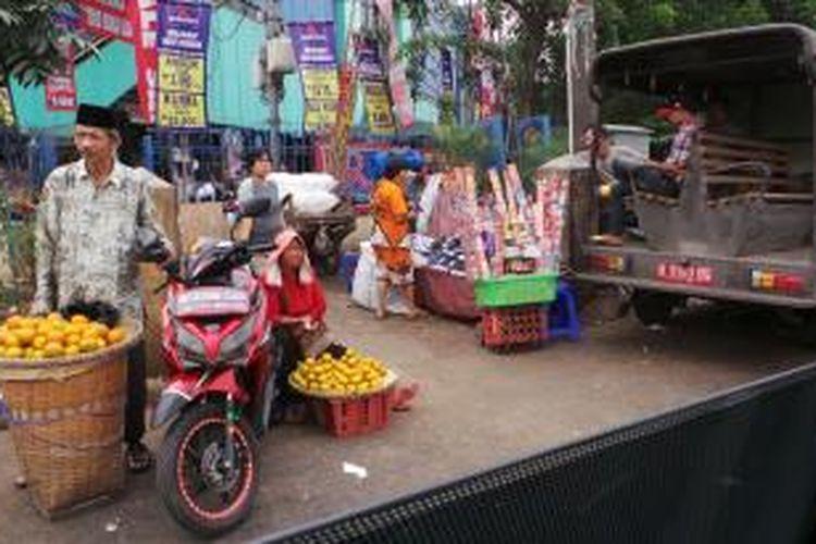 Pedagang kaki lima di Pasar Minggu menggunakan bahu jalan untuk menjual dagangannya, Senin (29/7/2013). Tampak pula mobil Satpol PP di sekitar lokasi para PKL.
