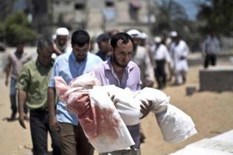 Warga Palestina yang berduka mengiringi pemakaman Abdallah Abu Ghazal, bocah laki-laki berusia lima tahun yang tewas akibat serangan udara Israel, di kota Beit Lahiya, utara Gaza, 10 Juli 2014. Serangan tersebut menewaskan 22 orang dan lima di antaranya adalah anak-anak.