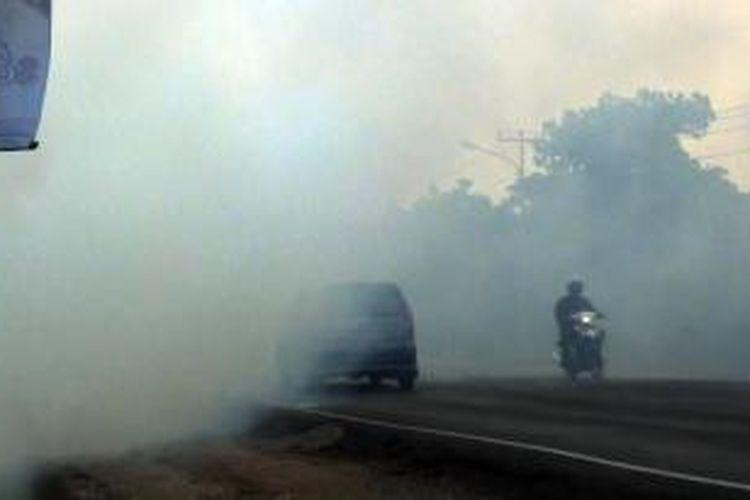 Jalan lintas timur (jalintim) Palembang-Ogan Ilir km 29 tertutup asap tebal sisa kebakaran lahan Minggu petang (23/8/2015).