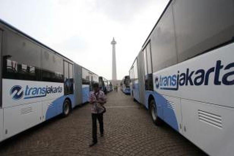 Warga melintasi bus transjakarta gandeng merek Scania di kawasan Monas, Jakarta, Senin (22/6/2015). PT Transjakarta hari ini meluncurkan 20 unit bus gandeng merek Scania bertepatan dengan peringatan HUT Ke-488 DKI Jakarta. Bus memiliki kapasitas hingga 140 orang dengan 39 kursi, termasuk 6 kursi prioritas dan 2 ruang untuk pengguna kursi roda.