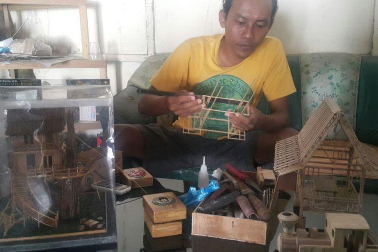 Singgih sedang merangkai stik bambu untuk dijadikan kerajinan.
