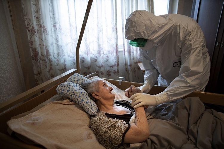 Dalam foto yang diambil pada Senin, 1 Juni 2020, Pastor Vasily Gelevan, mengenakan setelan biohazard dan sarung tangan untuk melindungi diri dari virus corona. Dia tampak berbicara kepada Lyudmila Polyak (86), yang diduga terinfeksi virus corona, di apartemennya di Moskwa , Rusia. Selain tugas rutinnya sebagai imam Ortodoks Rusia, Pastor Vasily mengunjungi orang-orang yang terinfeksi Covid-19 di rumah dan rumah sakit mereka