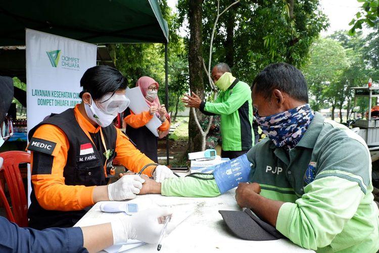 Petugas medis Dompet Dhuafa memeriksa kesehatan para petugas penggali makam penanganan Corona (Covid-19) di TPU Pondok Ranggon,  Jakarta Timur, Senin (13/4/2020).