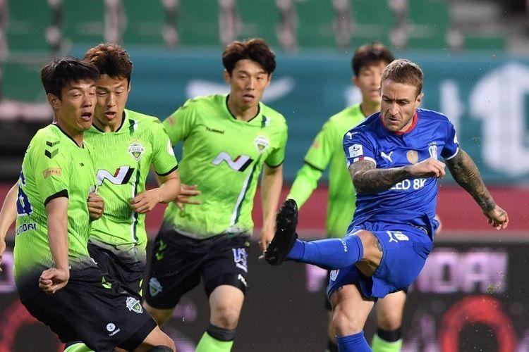 Suwon Samsung Bluewings Adam Taggart (kanan) menembakkan bola ke arah Jeonbuk Hyundai Motors selama pertandingan pembukaan pertandingan sepak bola K-League Korea Selatan di Stadion Piala Dunia Jeonju di Jeonju pada 8 Mei 2020.