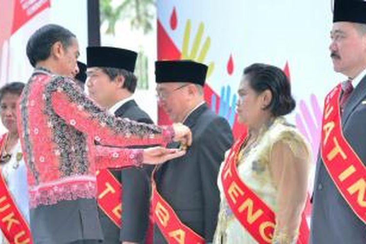 Presiden Jokowi menyematkan tanda kehormatan Satyalencana kepada para relawan yang telah mendonorkan darahnya sebanyak 100 kali di Istana Bogor, Jumat (18/12/2015).