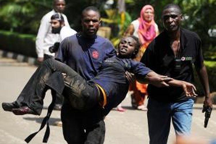 Seorang pria membopong seorang perempuan yang terluka setelah sekelompok orang bersenjata menyerbu sebuah pusat perbelanjaan di Nairobi, Kenya dan menembaki pengunjung.
