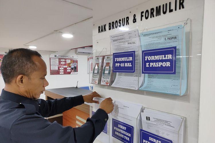 Petugas security tengah merapikan formulir pada rak brosur dan formulir di Unit Layanan Paspor (ULP) Plaza Semanggi, Jakarta Pusat, Selasa (3/3/2020).