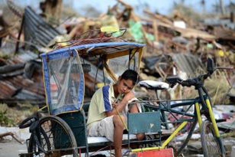 Seorang korban selamat terjangan topan Haiyan, beristirahat di atas sebuah becak di kota Tacloban, Filipina yang luluh lantak. Dikhawatirkan 10.000 orang tewas akibat terjangan topan dahsyat itu.