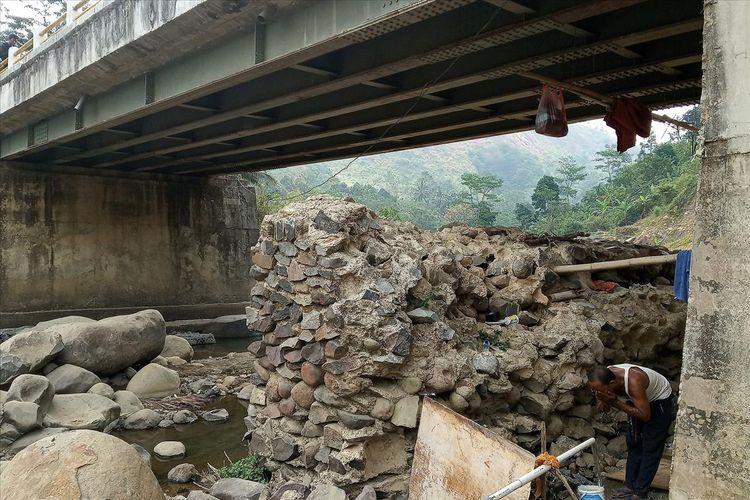 Seorang warga terpaksa melakukan aktivitas mandi, cuci dan kakus (MCK) di kamar mandi buatan yang berada di bawah jembatan Ciomas Jalan Nyengkle Gunung Batu, Desa Sukaharja, Kecamatan Sukamakmur, Kabupaten Bogor, Jawa Barat.