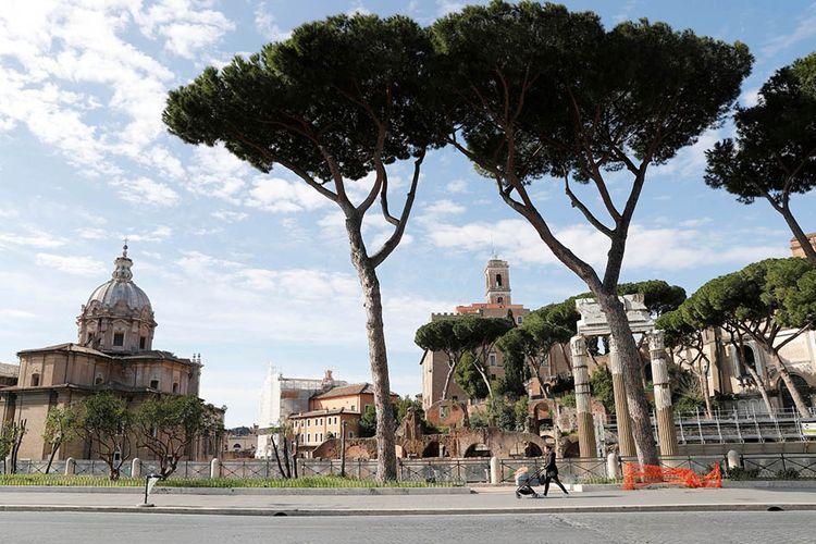 Seorang wanita berjalan dengan kereta bayi di sepanjang Via dei Fori Imperiali yang kosong, saat Italia melakukan tindakan tegas untuk mencegah penyebaran virus COVID-19, di Roma, Italia, Senin (23/3/2020).