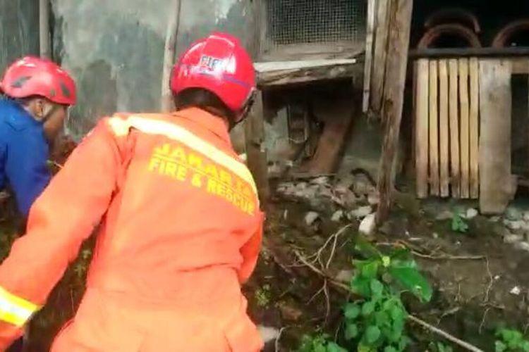 Petugas Suku Dinas Penanggulangan Kebakaran dan Penyelamatan (Sudin PKP) Jakarta Timur saat evakuasi seekor Ular Koros di dalam kawasan pemakaman, Jalan Gandaria, Gang Idaman, RW 09, Pasar Rebo, Jakarta Timur, Jumat (14/2/2020).