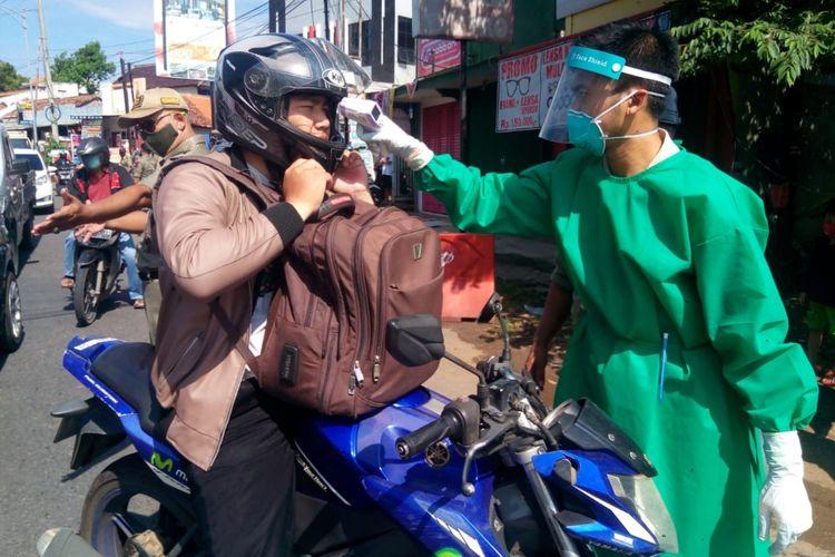 Pengecekan suhu pengemudi yang dilakukan oleh petugas berbaju hazmat di Pos Pantau Ngaliyan dekat jembatan tol, Senin (27/4/2020)