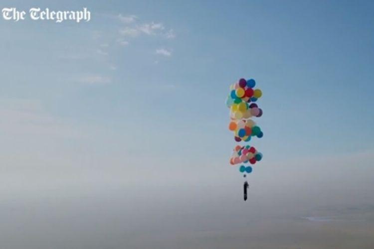 Pria Inggris, Tom Morgan saat terbang di langit Afrika Selatan menggunakan balon helium berwarna-warni.