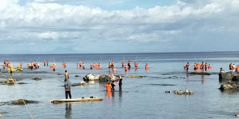 Ratusan warga mengenakan kaos seragam berwarna oranye, berjalan menuju laut membawa bambu dengan panjang antara 5 hingga 6 meter dan mengikuti lomba memancing tradisional di Pantai Carita, Kabupaten Pandeglang, Banten, Selasa (12/2/2019).