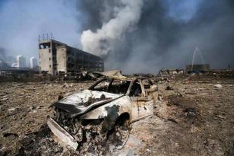 Mobil yang terbakar di lokasi ledakan dahsyat di Tianjin, Tiongkok, 13 Agustus 2015. Dua ledakan besar mengoyak kawasan industri tempat gas dan bahan kimia beracun, menewaskan setidaknya 44 orang dan 520 orang terluka.
