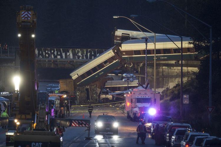 Petugas sedang mengamankan jalur I-5 ke arah selatan, di tempat tergelincirnya kereta Amtrak pada Senin (18/12/2017), di DuPont, Washington, Amerika Serikat. (AFP/Stephen Brashear)