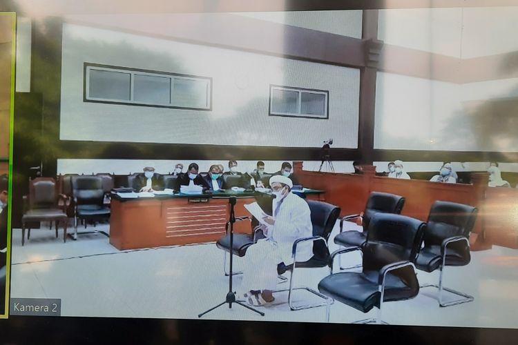 Rizieq Shihab menyebut, kasusnya bukan kasus hukum, tetapi dendam politik oligarki. Hal itu disampaikan Rizieq ketika membacakan pledoinya atas tuntutan jaksa terkait kasus kerumunan di Petamburan, Jakarta Pusat dan Megamendung, Kabupaten Bogor yang menjeratnya. Foto diambil pada Kamis (20/5/2021).