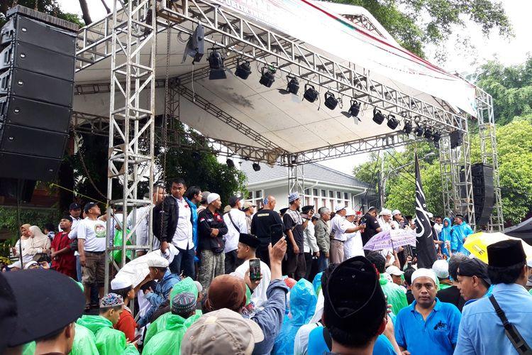 Massa di depan Rumah Prabowo lakukan doa bersama dan bacakan shalawat di bawah guyuran hujan, Jumat (19/4/2019).