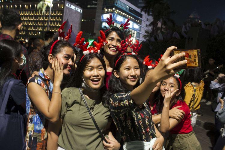 Warga mengambil swafoto saat menonton Christmas Carol di depan Grand Hyatt, Gondangdia, Menteng, Jakarta Pusat, Kamis, (19/12/2019). Tak hanya di bundaran HI, event ini juga digelar sejumlah spot ruang publik di sepanjang MH Thamrin - Sudirman.