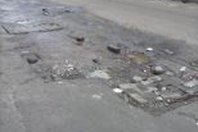 Kondisi jalan berlubang yang ditutupi dengan batu bata di Jalan Jembatan Besi Raya, Tambora, Jakarta Barat, Jumat (25/7/2014).