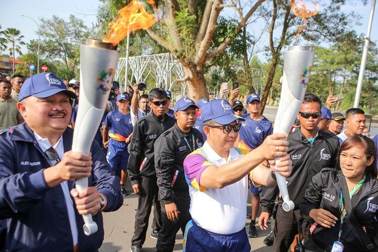 Kapolri Jenderal Pol Tito Karnavian (kedua kanan) dan Gubernur Sumatera Selatan Alex Noerdin (kiri) berlari sambil membawa obor api Asian Games 2018 di Jakabaring Sport City (JSC), Palembang, Sumatera Selatan, Sabtu (4/8/2018). Obor api Asian Games 2018 tersebut dibawa mengelilingi kota Palembang dan menyusuri Sungai Musi, selanjutnya akan menuju sejumlah kabupaten/kota yang ada di Sumatera Selatan.