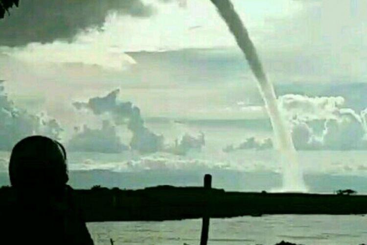 Seorang tengah menyaksikan penampakan angin puting beliung yang bergerak diatas permukaan Danau Tempe, Kabupaten Wajo, Sulawesi Selatan. Selasa, (27/2/2018).
