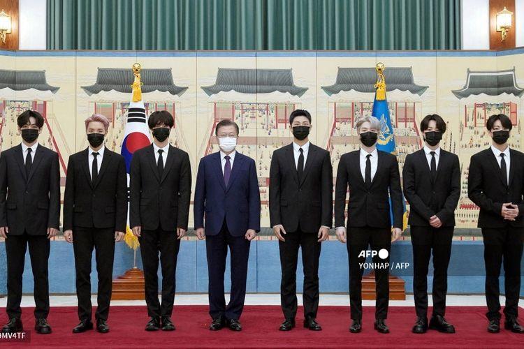 Presiden Korea Selatan Moon Jae In (keempat dari kiri) berfoto dengan para member BTS usai penyerahan surat penunjukan sebagai utusan khusus presiden dan paspor diplomatik di kantor kepresidenan Blue House di Seoul, Selasa (14/9/2021).