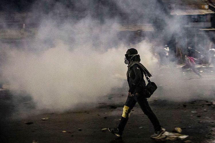 Seorang pengunjuk rasa berjalan melewati gas air mata saat terjadi kericuhan di kawasan Pejompongan, Jakarta, Kamis (26/9/2019). Demo yang melibatkan pelajar dari berbagai tingkatan menengah ke atas dan diwarnai kericuhan pada Rabu kemarin masih terkait aksi penolakan UU KPK dan RKUHP yang telah bergulir di sejumlah daerah sejak awal pekan.