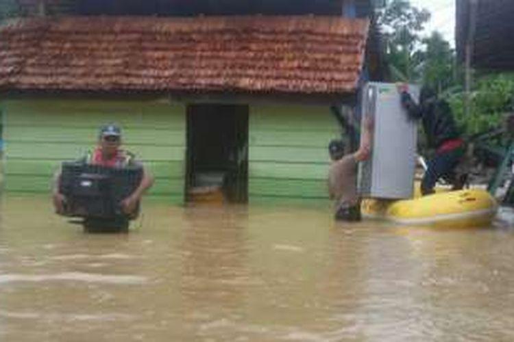 Sejumlah petugas polisi terlihat mengevakuasi perabotan rumah  milik warga yang menjadi korban banjir di kabupaten Konawe Utara