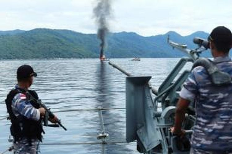 Anggota TNI AL memantau penenggelaman kapal milik nelayan asing di Perairan Anambas, Kepulauan Riau, Jumat (5/12/2014). Sebanyak tiga kapal Vietnam yang ditangkap TNI AL ditenggelamkan sebagai sikap tegas pemerintah Indonesia terhadap aksi pencurian ikan yang merugikan negara hingga Rp 300 triliun per tahun.