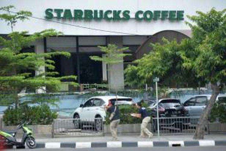 Polisi berpakaian sipil mengarahkan pistol ke arah terduga pelaku di luar sebuah kafe setelah ledakan menghantam kawasan Jalan MH Thamrin, Jakarta Pusat, 14 Januari 2016. Serangkaian ledakan menewaskan sejumlah orang, terjadi baku tembak antara polisi dan beberapa orang yang diduga pelaku.