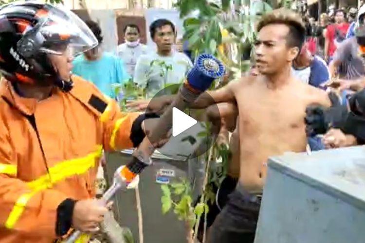 Tangkapan layar video saling dorong antara warga dan petugas pemadam kebakaran di Jalan Kutai Indah, RT 40, Desa Sangatta Utara, Kecamatan Sangatta, Kutai Timur, Kalimantan Timur, Selasa (30/3/2021).