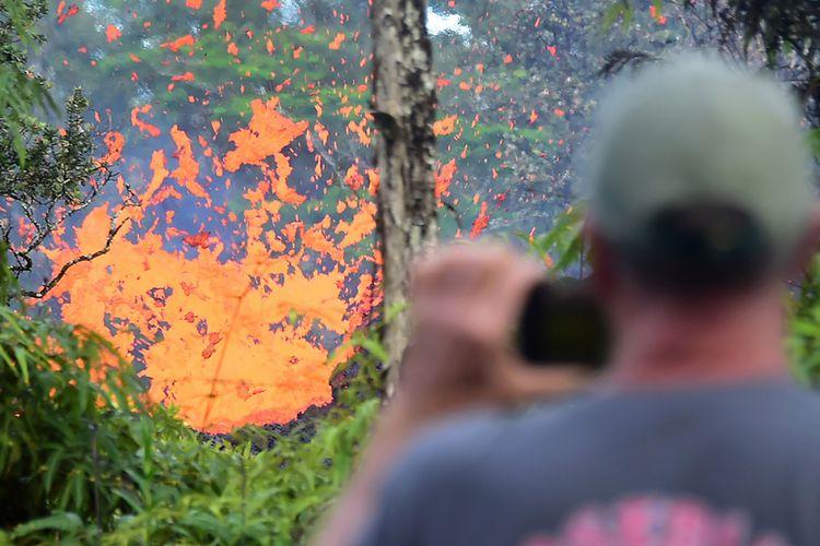 Seorang pria melihat semburan lahar yang muncul dari retakan terlihat di kawasan Leilani Estates di Hawaii, Jumat (4/5/2018). Letusan Gunung Kilauea diawali guncangan gempa berkekuatan magnitudo 6,9 yang memicu runtuhnya tebing pantai dan memuntahkan lahar di kawasan yang dekat dengan permukiman, memaksa ribuan orang untuk dievakuasi.