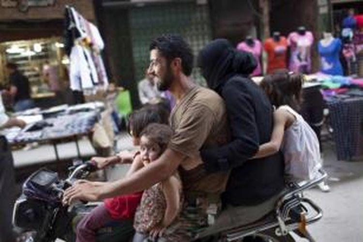 Sebuah keluarga mengendarai sepeda motor di depan pasar di Kota Aleppo, Suriah, 14 September 2013.