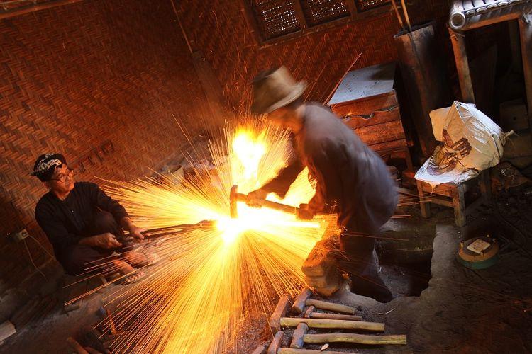 Empu Sungkowo Harumbrojo tengah memanaskan besi yang akan ditempa di besalen miliknya di Dusun Gatak, Desa Sumberagung, Kecamatan Moyudan, Kabupaten Sleman, Rabu (20/9/2017).