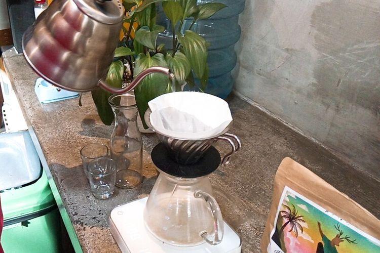 Barista 'mencuci' V60 dan kertas filter menggunakan air panas untuk membuat es kopi Bali Kintamani di Malbourne Coffee Co, Kota Malang, (8/1/2021).