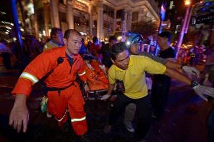 Petugas media bergegas menolong korban luka-luka akibat ledakan bom dekat Kuil Erawan di pusat Kota Bangkok, Thailand, Senin (17/8/2015) malam.