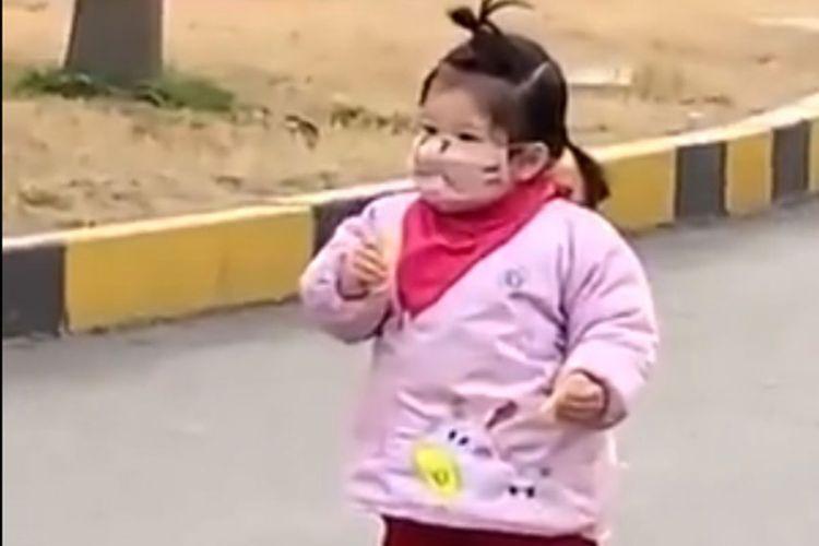 Seorang anak balita di Haozhou, provinsi Anhui di China Timur coba memakan biskuit, tapi upayanya sia-sia karena lupa mulutnya tertutup masker (25/2/2020).