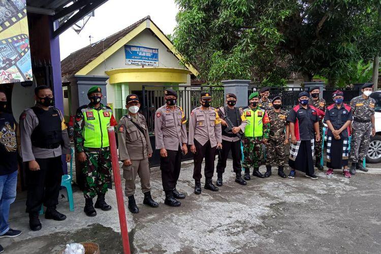Anggota Banser dan Pecalang melakukan penjagaan bersama personel TNI dan Polri di sebuah gereja di Kecamatan Talun, Kabupaten Blitar, Jumat (2/4/2021)