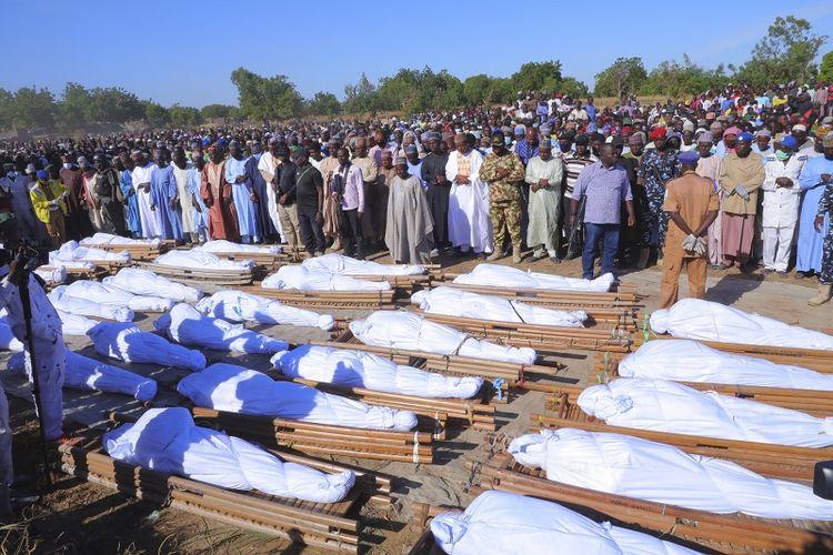 Orang-orang menghadiri pemakaman para petani yang dibantai oleh tersangka militan Boko Haram di Zaabarmar, Nigeria, Minggu, 29 November 2020.  Para pejabat Nigeria mengatakan tersangka anggota kelompok militan Boko Haram telah membunuh sedikitnya 40 petani padi dan nelayan saat mereka memanen padi di Negara Bagian Borno utara. Serangan itu dilakukan pada hari Sabtu di sawah di Garin Kwashebe, sebuah komunitas Borno yang terkenal dengan pertanian padi.