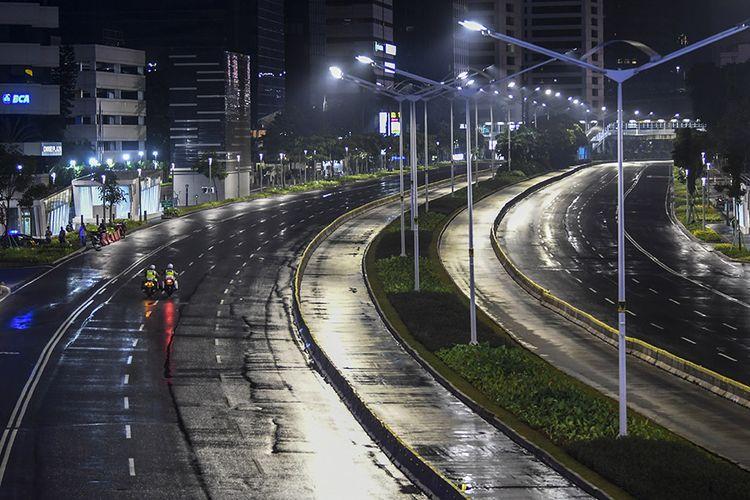 Petugas kepolisian melakukan patroli saat diberlakukannya Car Free Night (malam bebas kendaraan) dan Crowd Free Night (malam bebas keramaian) pada malam pergantian tahun di kawasan Jalan Sudirman, Jakarta, Kamis (31/12/2020). Polda Metro Jaya melakukan Car Free Night dan Crowd Free Night dengan menutup sepanjang Jalan Sudirman-MH Thamrin, Jakarta pada malam pergantian tahun untuk mencegah kerumunan warga.