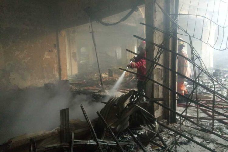 Petugas pemadam kebakaran saat memadamkan sisa api yang membakar pasar Weleri. KOMPAS.COM/SLAMET PRIYATIN