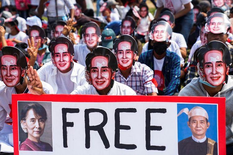 Pengunjuk rasa memakai topeng mirip pemimpin yang digulingkan Aung San Suu Kyi, memperlihatkan salam tiga jari saat mereka berpartisipasi dalam sebuah protes terhadap kup militer di Yangon, Myanmar, Minggu (28/2/2021). ANTARA FOTO/REUTERS/Stringer/WSJ/cfo