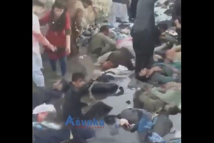 Potongan gambar dari video menunjukkan kerumunan dan korban terluka berkumpul saat serangan bom bunuh diri mengguncang kawasan bandara di Kabul, Afghanistan, pada 26 Agustus 2021. Dua pelaku bom bunuh diri dan kelompok bersenjata menyerang kerumunan di bandara, di tengah proses evakuasi warga Afghanistan setelah Taliban berkuasa.