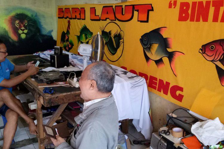 Achmadi (kanan), salah satu pelanggan setia spanduk lukis Hartono (kiri) yang kembali datang untuk memesan spanduk Soto Lamongan, Selasa (30/5/2017). Achmadi adalah seorang pengusaha soto yang memiliki enam cabang di Bekasi. Sejak delapan tahun belakangan, Achmadi jatuh cinta pada karya Hartono.