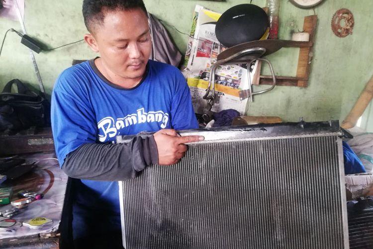 Teknisi bengkel spesialis radiator menunjukkan salah satu contoh radiator