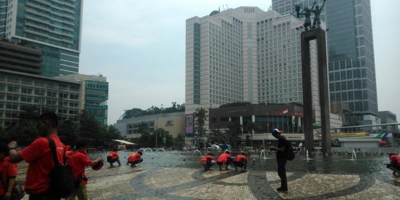 Buruh mengambil air wudu Bundaran HI, Jakarta Pusat, Jumat (1/5/2015).