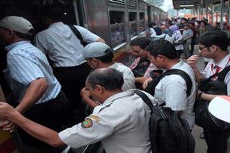 Penumpang menaiki armada  KRL Ekonomi Palmerah-Serpong di Stasiun Palmerah, Jakarta Pusat, Senin (6/5/2013). Mulai hari ini, Selasa (7/5/2013), Seluruh perjalanan KRL Ekonomi di lintas Tanah abang-Serpong dihapus dan digantikan rangkaian Commuter Line.