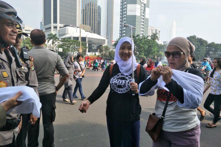 Satuan Polisi Pamong Praja (Satpol PP) DKI Jakarta membagikan kaus putih polos untuk warga yang mengenakan kaus dengan tanda pagar #2019GantiPresiden di kawasan Car Free Day (CFD) di Jalan Sudirman-Thamrin, Jakarta Pusat, Minggu (6/5/2018).