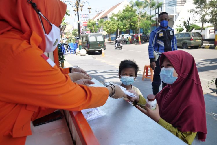 BAGI MASKER DAN SUSU—Petugas BPBD Kota Madiun membagikan susu dan masker gratis di Gerai Masker Gratis bagi anak-anak agar imunitas  terjaga dan disiplin menjalankan protokol kesehatan, Senin (26/7/2021).